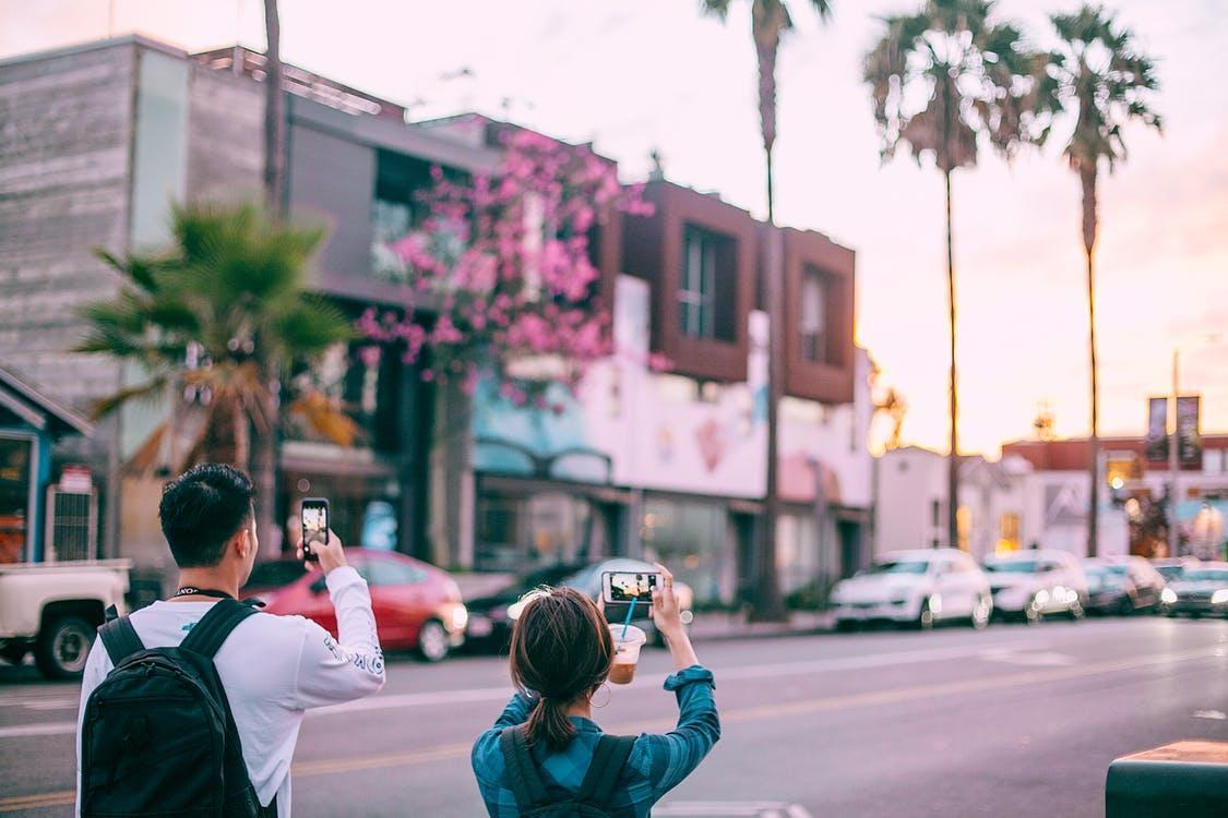 Unrecognizable tourists taking pictures on smartphone of tropical city street