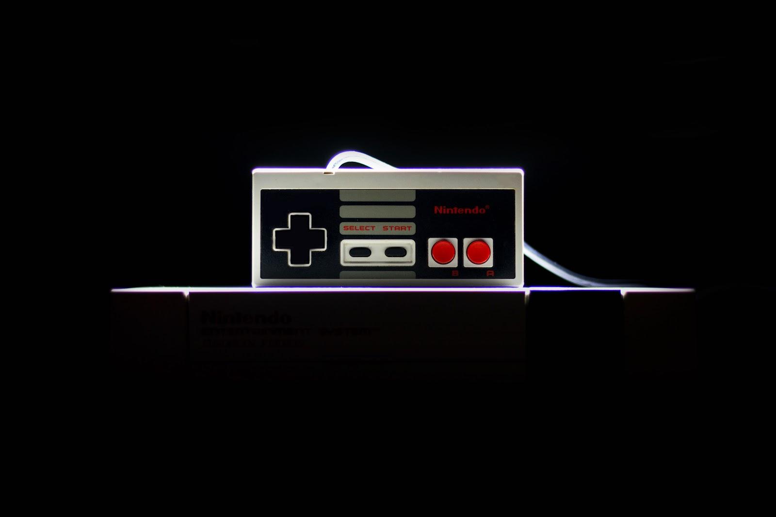 a retro Nintendo controller against a black backdrop