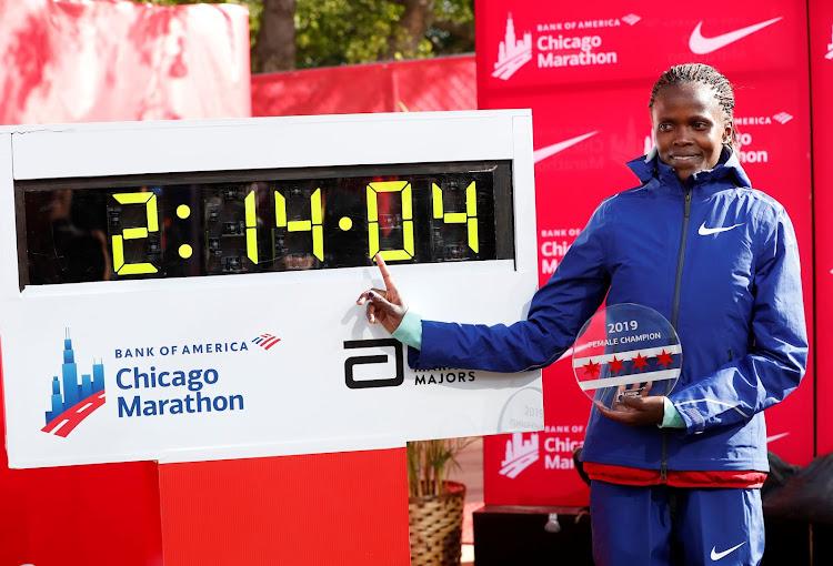 Kenya's Brigid Kosgei celebrates winning the women's marathon next to her new world record time.
