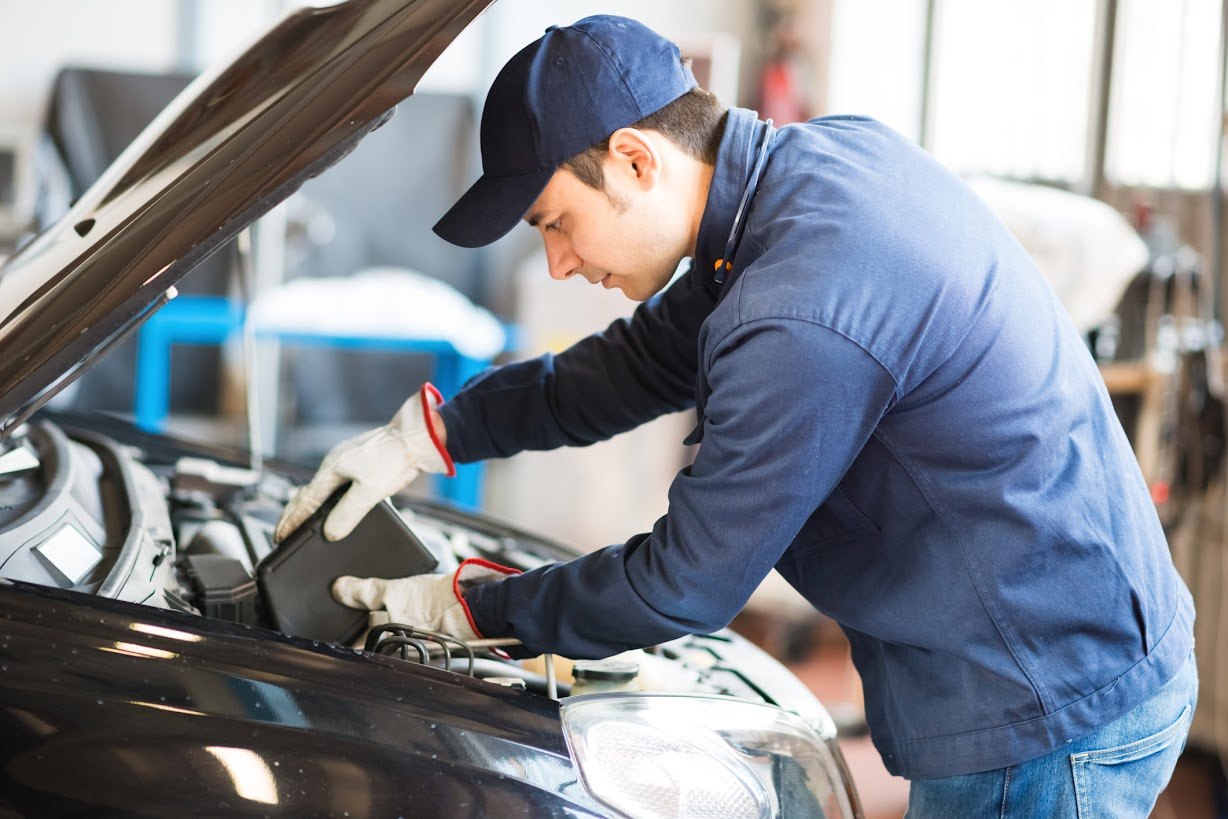 Mechanic performing oil change at A+ Japanese Auto Care in San Carlos, CA