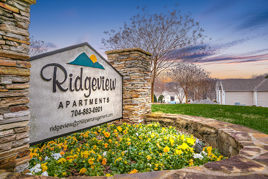 Property sign for Ridgeview surrounded by greenery at dusk