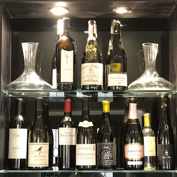 a variety of wines on glass shelves with decanters