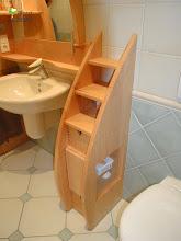 Photo: In Vogelaugenahorn massiv. Das Mittelteil mit Schubladen sprengt den verspiegelten, runden Überbau. Praktisch auch das seitliche Ablagefach in dem Regal als Abtrennung zum WC.