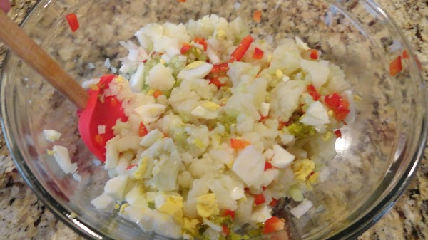 Chopped eggs, onion, celery, peppers and pickles mixed together in bowl