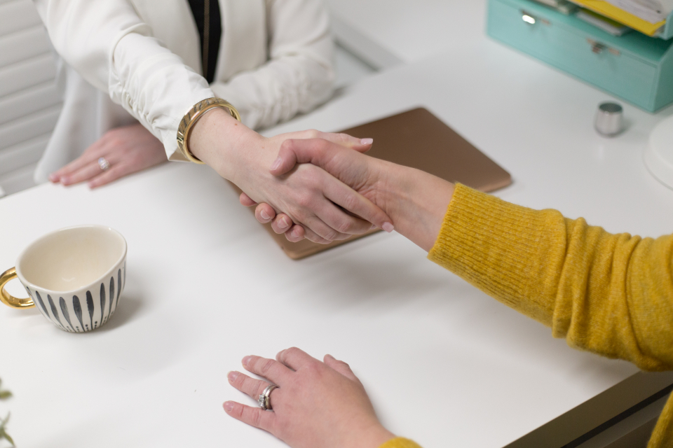Alt-text: two people shaking hands across a table
