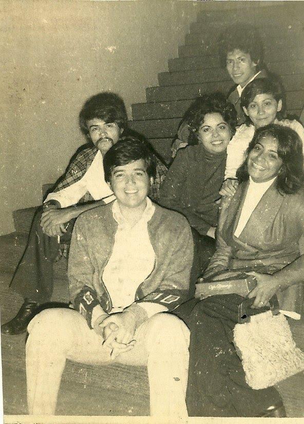 Foto blanco y negro de un grupo de personas sentadas posando para una foto  Descripción generada automáticamente