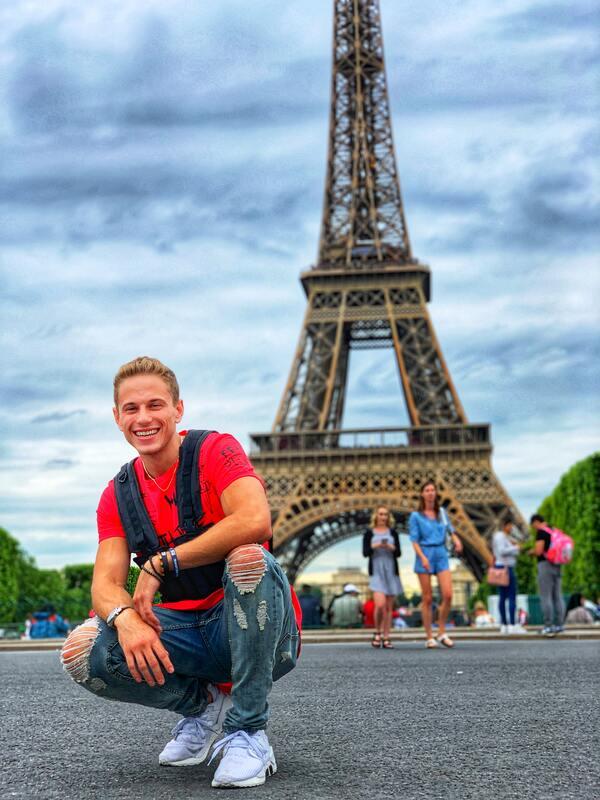 homem posando em frente a torre eifel