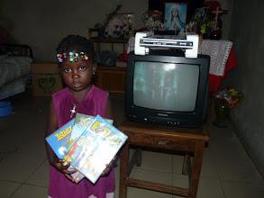 Photo: Ariké reçoit des DVD, pour utiliser davantage le téléviseur reçu l'an passé