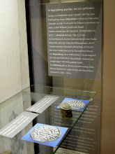 Photo: Silberner Denar Herzog Heinrichs II. Auf der Vorderseite ist ein Kreuz zu sehen, in drei Winkeln jeweils eine Kugel. Darüber ist die (verbalhornte) Umschrift zu lesen: 'HEIMRICVS DVX'. Auf der Rückseite ist eine Letternkirche mit zwei Stufen zu erkennen, darin der Münzmeister 'RAT', darüber 'REGHINA CIVITAS', also Regensburg. Inventar-Nummer im LMO: 2340 L., Dm. 22,5 mm.  Der Denar stammt aus der herzoglichen Münze von  Regensburg. Wahrscheinlich wurde er unter dem Herzog Heinrich II. ('dem Zänker') geprägt (948-955/985-995). Er stammt also noch nicht aus der Zeit seines Sohnes, des Herzogs Heinrich IV, der später als König bzw. Kaiser Heinrich II. regierte (1002-1024).