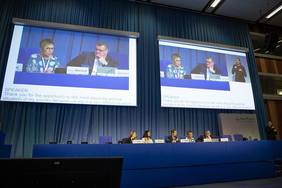 Cinco pessoas sentadas atrás de uma mesa azul. No fundo, duas telas com a projeção da mesa, bem como recursos de acessibilidade. No lado direito, uma intérprete de língua de sinais.
