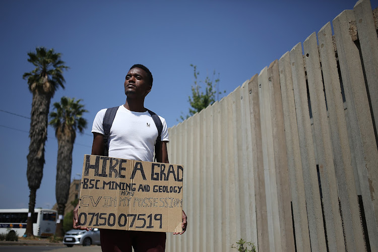 Braamfontein, Johannesburg. Mashau Glen Ndouvhada, POSES for a picture holding a cardboard box. He claims to have a B.S.C in Mining and Geology and is looking for employment .