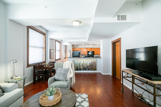 Model unit living room, facing the kitchen, with wood plank floors, white walls, windows with wood trim, and furniture