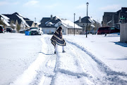 A man walks to his friend's home in a neighbourhood without electricity as snow covers the BlackHawk neighborhood in Pflugerville, Texas, US February 15, 2021.