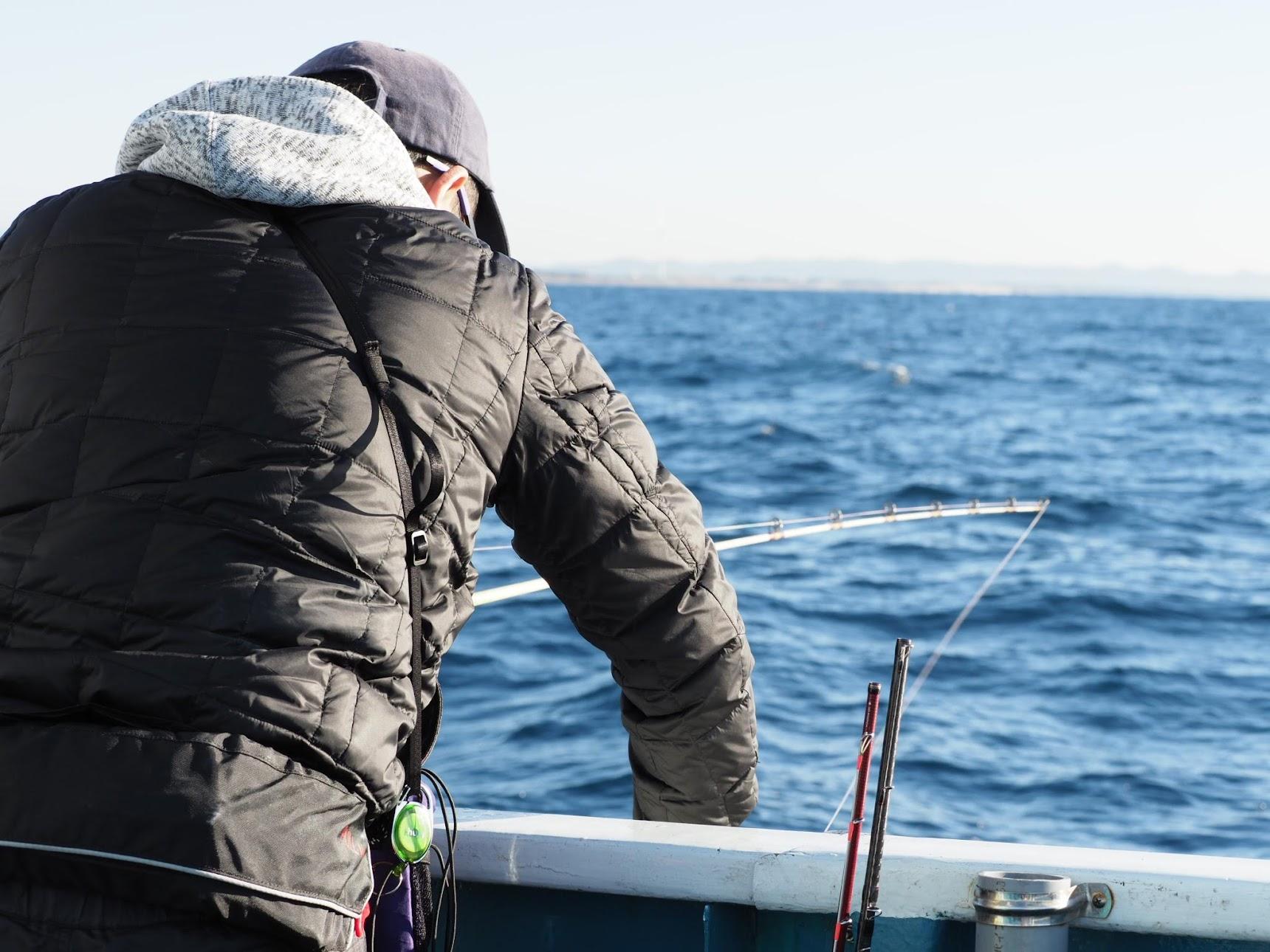 仕掛けを引き上げる釣り人