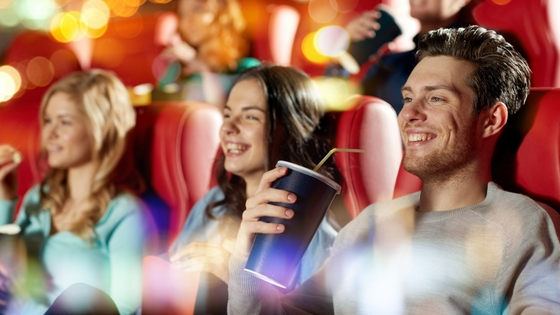 a row of people in a movie theatre enjoy popcorn and drinks