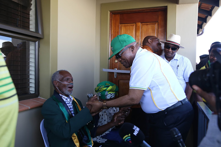 Former president Jacob Zuma greets Struggle veteran Amos Ndwalane during the handing over of his new house in Lamontville in Durban on Friday.