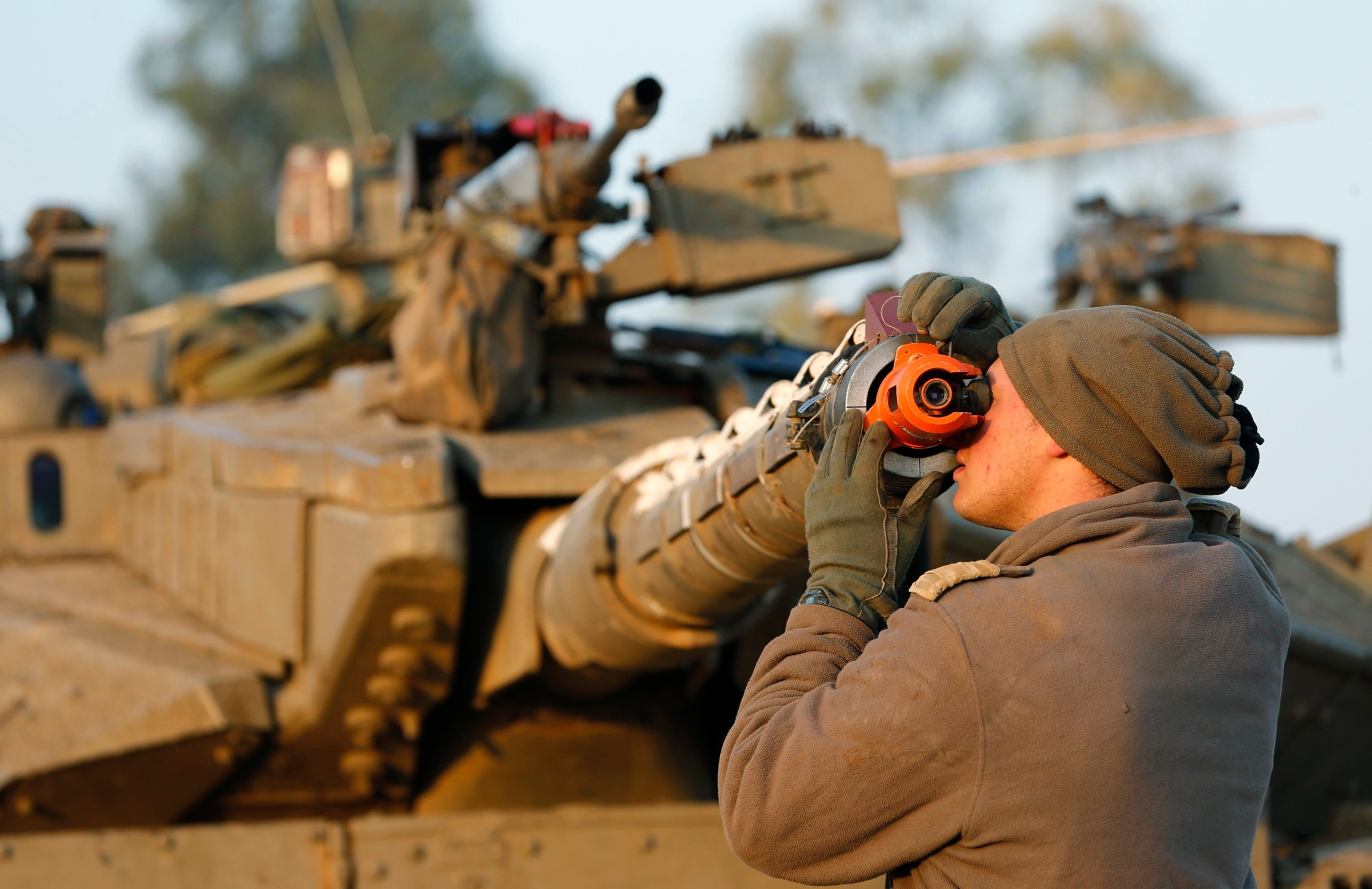 Photo: An Israeli soldier checks the gun sighting on a main battle tank at a staging area near the border.