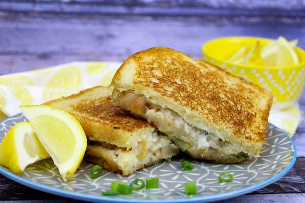 Crabby Grilled Cheese Sandwich On A Plate With Sliced Lemons.