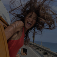 Woman leaning out car window, smiling with the ocean behind her