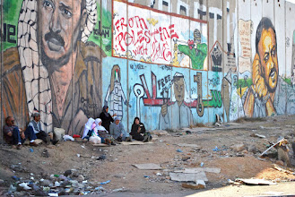 Photo: Palestinians sit outside Qalandiya checkpoint with the grafitti-covered apartheid wall behind them.