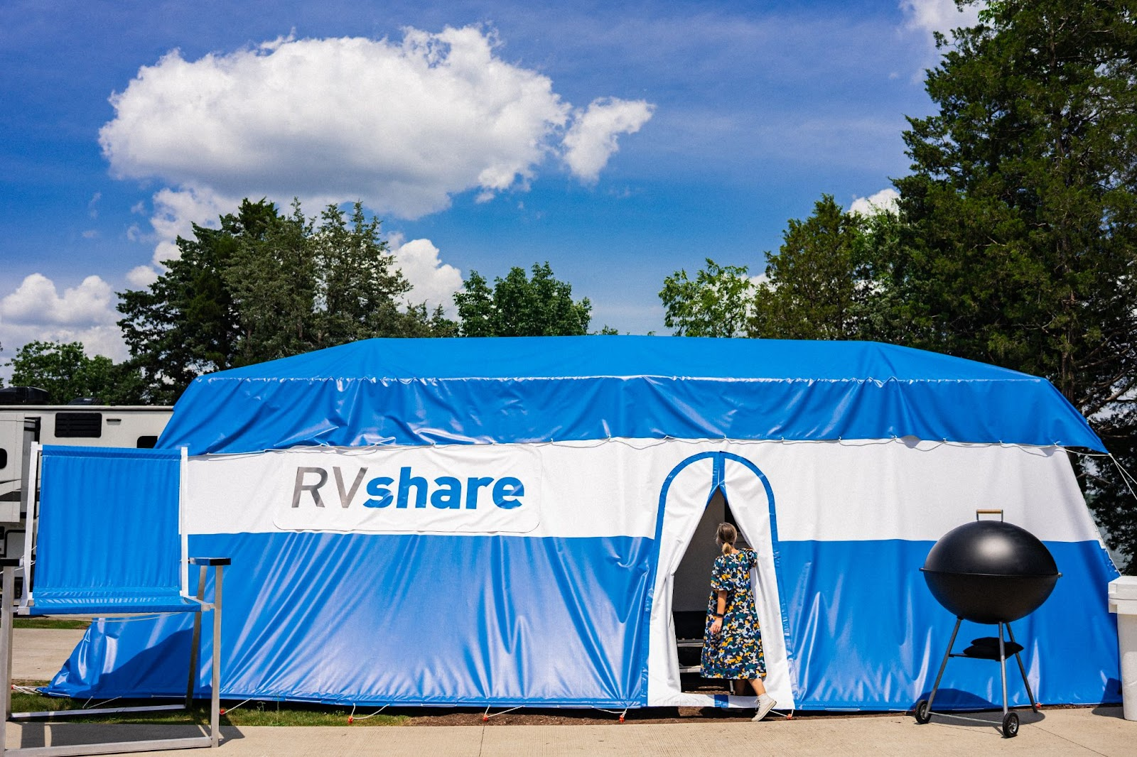 Large tent draped over an RV with an oversized camping chair and grill