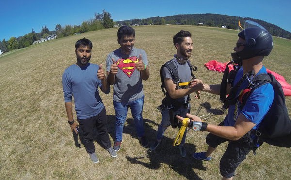 Joshua, Vishal, and Parthepan on the ground immediately after skydiving.