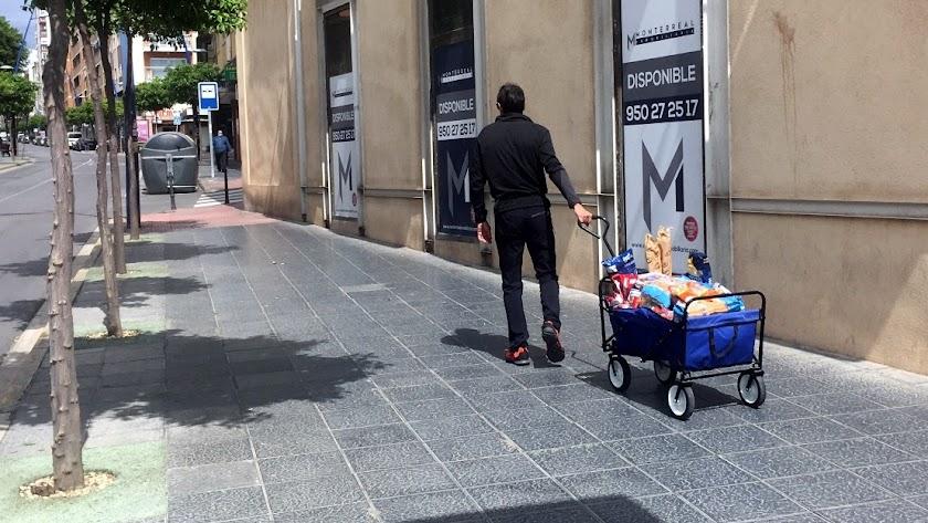 Un hombre  con su avituallamiento de alimentos en un carro caminando ayer por la Avenida Pablo iglesias.