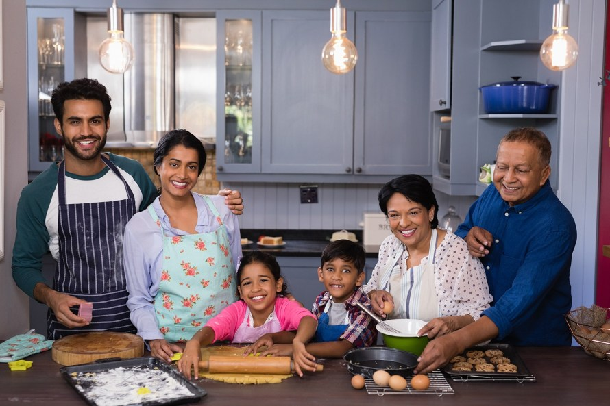 two kids, their parents, and grandparents baking together in a kitchen