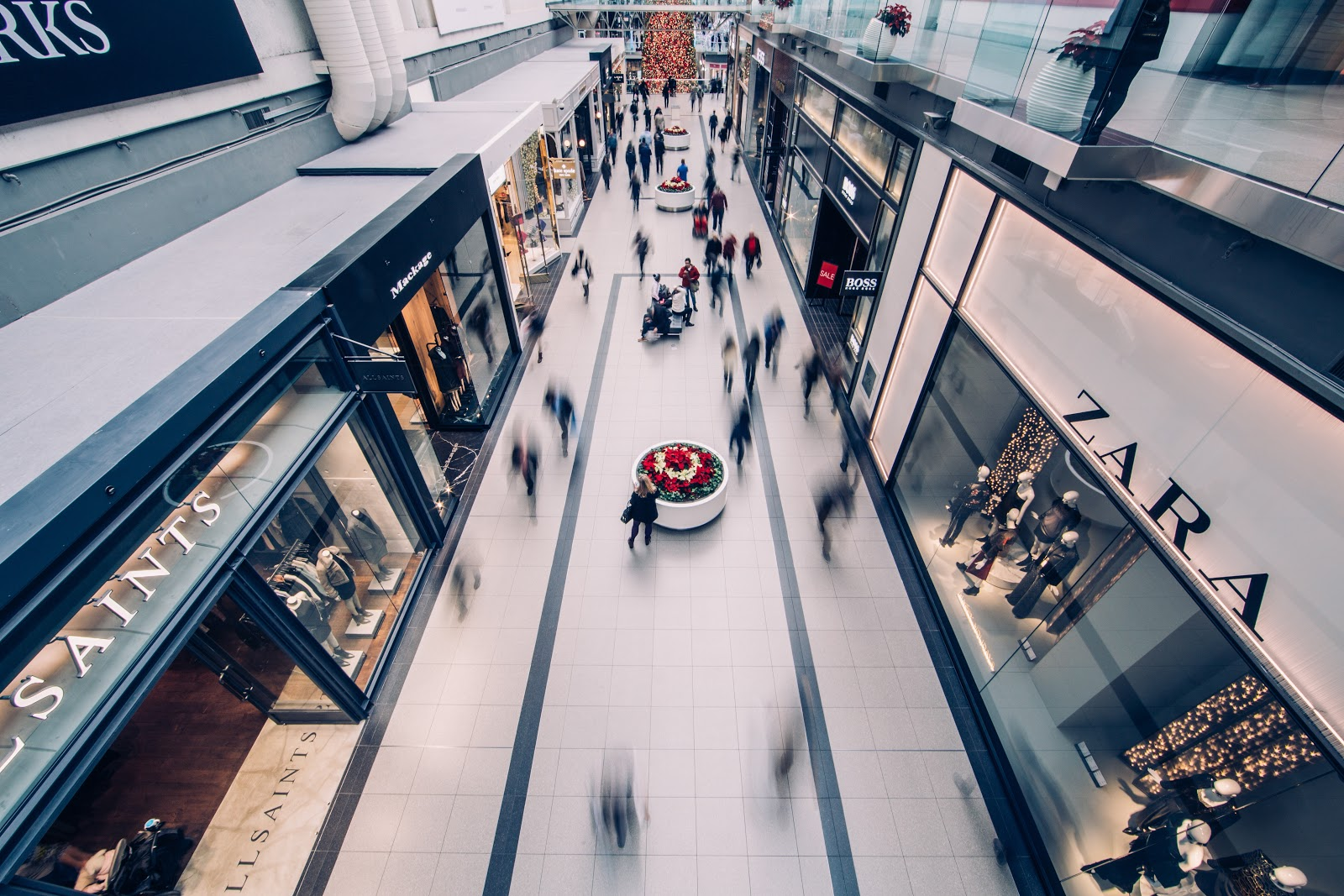 Customers walking,entering stores and shopping in a mall. Zara, Hugo Boss on the right, AllSaints, Mackage store on the left.