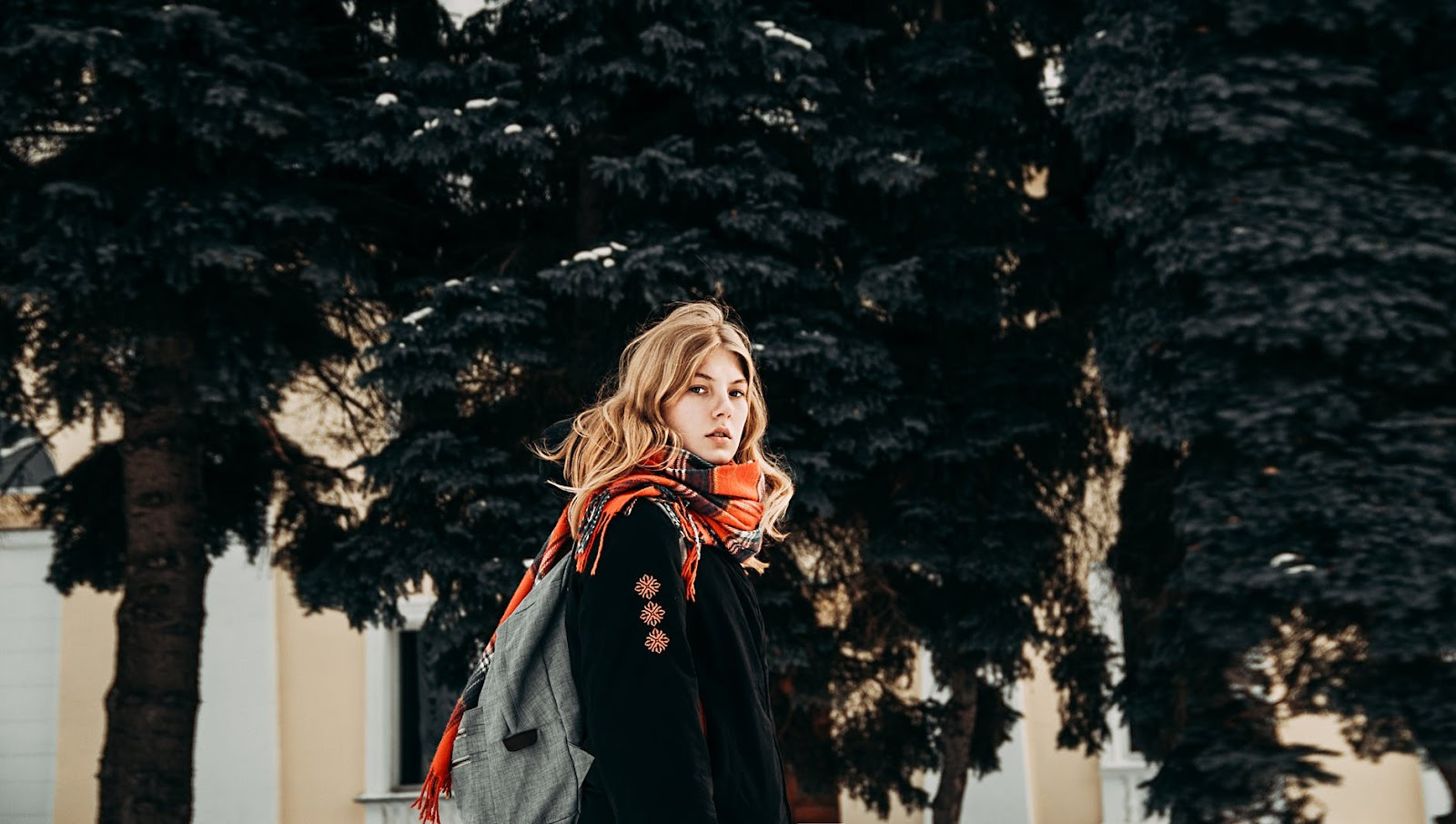 woman in big scarf and backpack looking at camera in trees