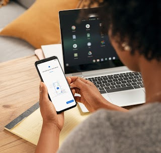 Woman sits at a desk, setting up her new mobile device for work.