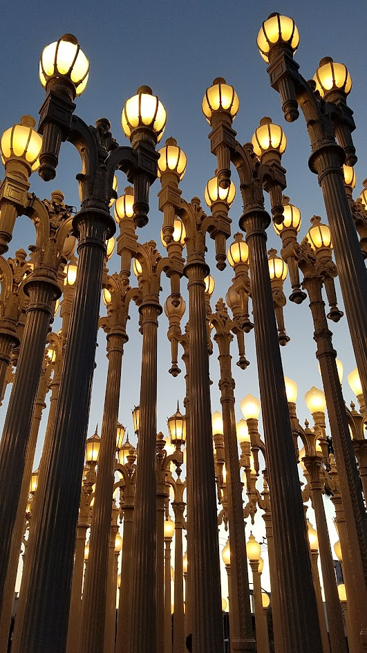 One of the most famous and free (since it is an outdoor sculpture) art you can see in the park at LACMA is the iconic Urban Lights. Created by Chris Burden, it is made of 202 restored street lamps in various styles based on where they were from (most are from southern California and some from Portland Oregon too!). The lamps are painted grey and assembled in a grid, and are solar powered and become lit in the evening.