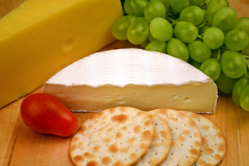 a wooden cheese board with crackers and grapes on it