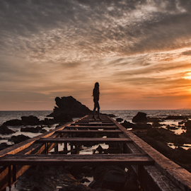 Woman on pier  by Gianluca Presto - Buildings & Architecture Bridges & Suspended Structures ( clouds, colorful, colors, sea, beach, sun, portrait, sky, girl, woman, sunset, pier, perspective, bridge, sunrise, rocks,  )
