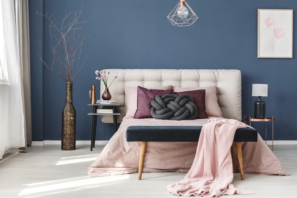 Um quarto com parede azul, uma cama com estofado rosa e um vaso decorativo.