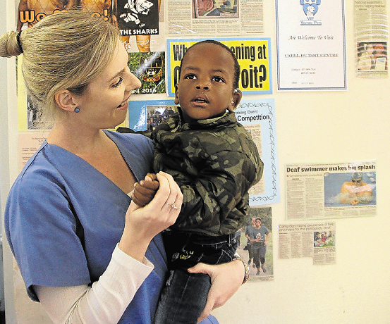 East London audiologist Catherine Richter with little Inothando Qalinto, 2, who could not have his cochlear implant connected yesterday and hear sound for the first time because thieves stole programming cables and computers necessary for the procedure. The items will be useless to the thieves as they are designed for a cochlear implant