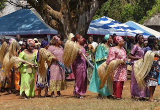 Photo: Auch viele wohlgekleidete Damen beteiligen sich an dem Schreittanz. In den Händen tragen sie die bei einer rituellen Feier unentbehrlichen Tanzwedel.