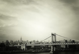 """Photo: """"...this was still a town that existed in black and white...""""  New York Photography: The New York City skyline and the Manhattan Bridge.  """"Chapter one. """"  """"He adored New York City. He idolized it all out of proportion. """"  Uh, no. Make that """"He romanticized it all out of proportion. """"  """"To him, no matter what the season was,  this was still a town that existed in black and white  and pulsated to the great tunes of George Gershwin. """"  If there is one opening sequence in cinema that perfectly illustrates even a tiny iota of the overwhelming love I have for New York City, it's the opening sequence to Woody Allen's Manhattan which you can view here: Manhattan (Opening) . I know that people have very definite ideas about Woody Allen but his early body of work still contains some of my favorite interpretations of life in Manhattan and this particular opening still chokes me up absolutely every time I watch it especially the montage from 1:52 on. I actually learned how to play Gershwin's Rhapsody in Blue on the piano when I was younger almost entirely because of this opening sequence :).  I was asked a while ago if I ever get bored or jaded about certain views or landscapes in New York City. I didn't really know how to answer the question without sounding like a blubbering idiot. I know many people seem to get bored of overly-photographed parts of New York City but for me, there is always something new and something special imparted to these landscapes based on each individual artist's perspective.  The photo in this post is of a landscape that overwhelms me every time I lay eyes on it. For me, this scene encompasses a feeling that is hard to express entirely in words. It's how the light falls onto the Manhattan Bridge embracing its architecture in a glow while the skyline gracefully pushes through the dreamy haze distilling the essence of New York City down to its purest forms of hope, beauty and possibility.    *This is a re-post from early August for newer followe"""