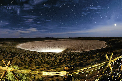 A floodlight illuminates a pan in the Kgalagadi Transfrontier Park.