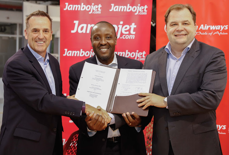 (R to L) KQ MD & CEO, Sebastian Mikosz with Jambo Jet MD & CEO Allan Kilavuka and Patrick Coulter, Director, FlightSafety International display the MoU that will see flight Safety International provide a Dash 8 Q400 simulator to support training and maintenance teams.