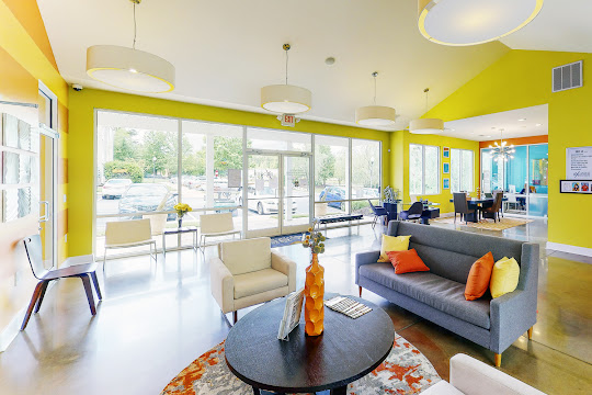 Community clubhouse with concrete flooring, gray couch, and green walls