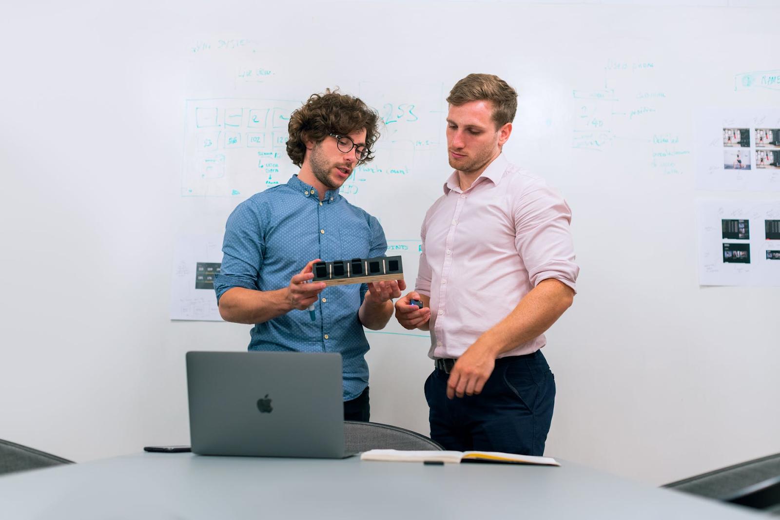 Homem mostrando para outro um projeto - levantamento de requisitos de software