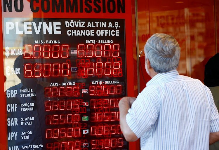 A man looks to a display board of a currency exchange office in Istanbul, Turkey. REUTERS/OSMAN ORSAL/FILE PHOTO