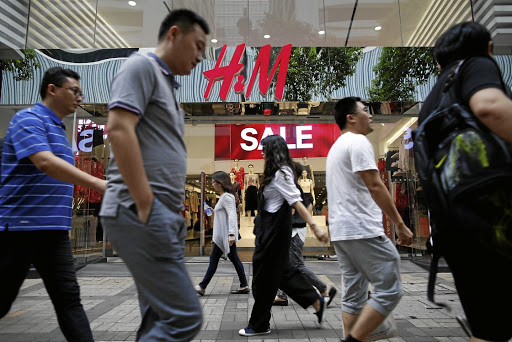 People walk past an H&M fashion chain store in Tsim Sha Tsui shopping district in Hong Kong, China. Picture: REUTERS