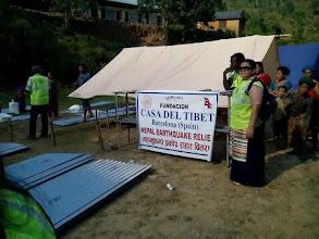 Photo: Nuestra representante Ringzing Dolma repartiendo láminas de metal para proteger las cabañas de las lluvias.