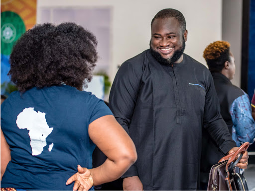 A man in traditional African clothing is smiling at a woman wearing a tshirt with the continent of Africa on the back.