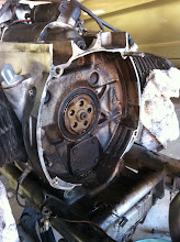 """Photo: It shouldn't be that filthy. This is an indication of the rear main seal (dark black circle around the center piece) and/or the oil pump cover seal (square cover below center) leaking. Oil seeps from the engine and gets flung around the cavity by the clutch. Also leaks down under the transmission onto that """"shelf"""" and then onto your clean garage floor."""