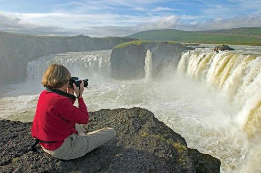 Lindblad-Expeditions-Iceland-Godafoss.jpg - A traveler photographs the magnificent Godafoss (Waterfall of the Gods) on the Sktalfandafljot River during a Lindblad Expeditions tour of Iceland.