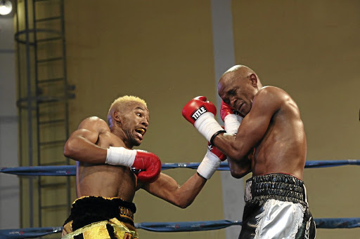 Azinga Fuzile, left, hits Malcolm Klassen with a left at Orient Theatre on Sunday. / MARK ANDREWS/ Daily Dispatch