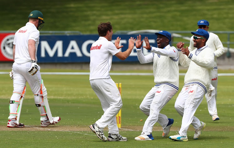 Michael Cohen of the Cobras celebrates with teammates after taking the wicket of Simon Harmer of the Warriors during day 2 of the Sunfoil Series 2017/18 Cricket match between the Cobras and the Warriors at Newlands Cricket Ground, Cape Town on the 17 October 2017.